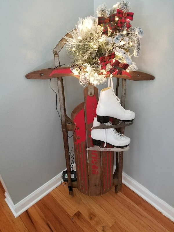 Pair Of White And Black Ice Skates Brown And Red Wooden Sled