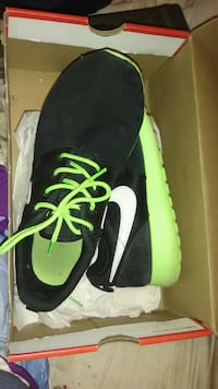 pair of black-and-green Nike running shoes
