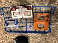three assorted-color handheld game consoles