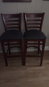 two black wooden framed black padded chairs 25 km