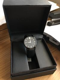 Round black analog watch with black leather strap in box