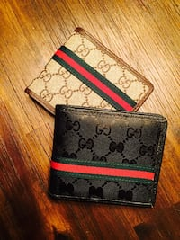 two black and white leather Gucci wallets