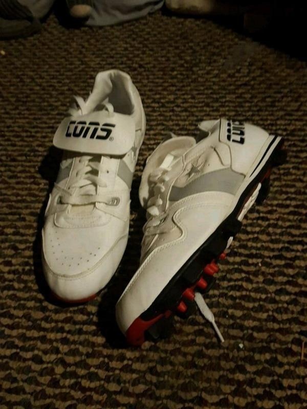 pair of white-and-black Nike football shoes