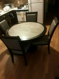 round black wooden table with five chairs