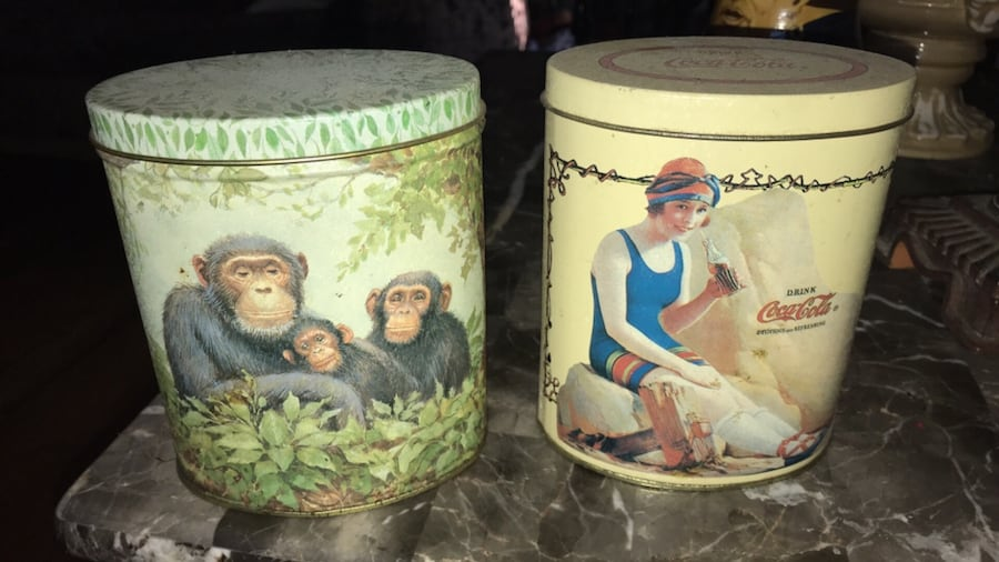 Two specialty cans. One Coca Cola the other a chimp family.  f25ede57-4db5-44c4-827a-7e00133e6b80
