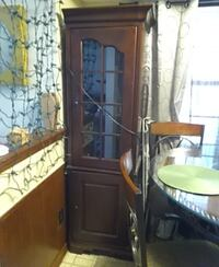 Two China cabinets lights inside glass shelves on top wooden shelf on