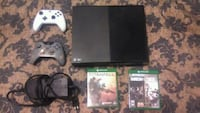 Black Xbox one with two controllers and two games