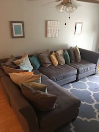 Gray suede sectional couch with throw pillows Oak Island