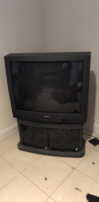 black CRT TV with brown wooden TV stand