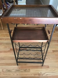 Wine holder table with glass top and tray.