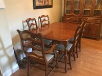 oval brown wooden dining table with six chairs set