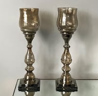 two brass-colored candle holders Mentor