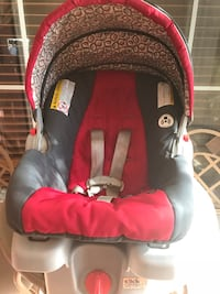 baby's red, black, and brown car seat carrier with car seat base