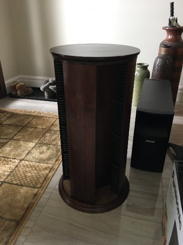 round brown wooden DVD tower rack