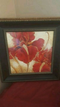 red irises painting and brown frame