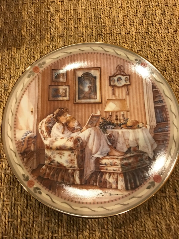 round brown and white woman holding book beside toddler while sitting on chair painted plate