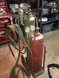 red and green acetylene tanks with torch and gauges