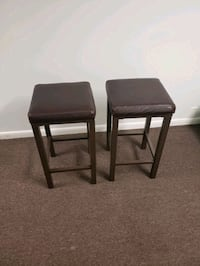 Two brown leather stools