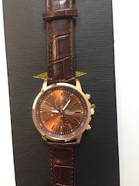Round silver analog chronograph watch with brown strap