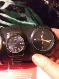 two black bezels analog watches with black link bracelets