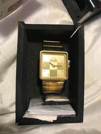 square gold-colored analog watch with link bracelet