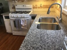 white gas range; stainless steel faucet