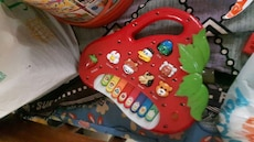red, white and green strawberry shaped learning piano toy