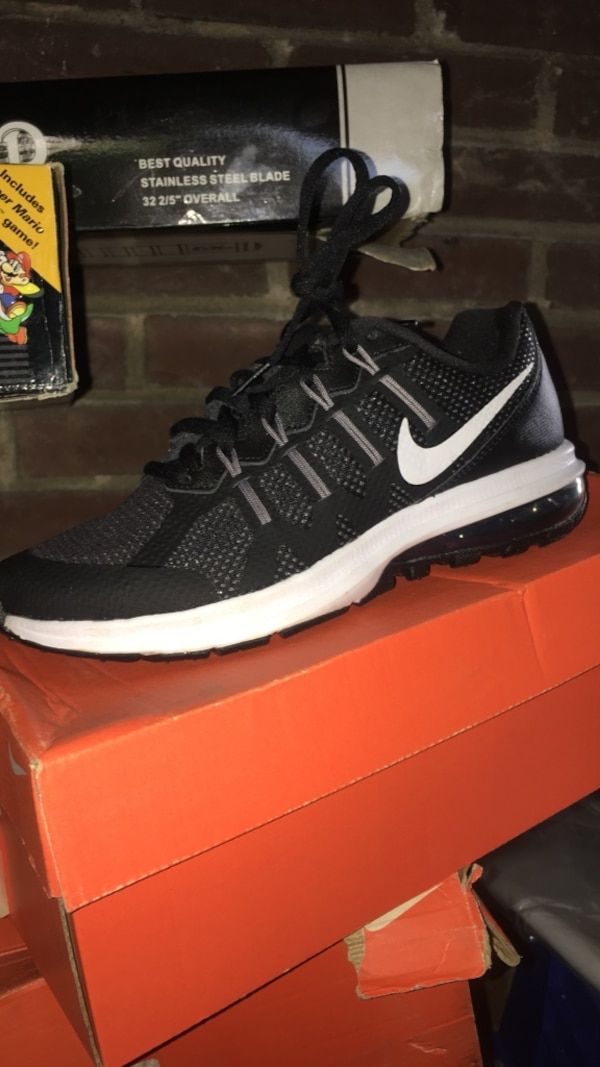 Unpaired black and white Nike running shoe with box