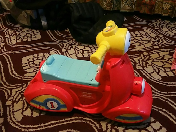 childre's red, yellow, and teal ride on toy