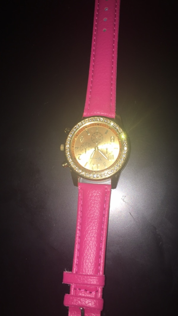 round gold-colored analog watch with pink leather strap