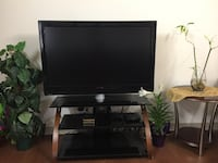 Black flat screen tv with black wooden tv stand New Westminster, V3M 3Z4