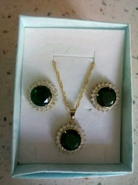 round gold-colored black and clear gemstone encrusted pendant and earrings set with box