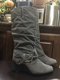 pair of gray buckled wedge boots