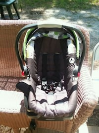 baby's black and brown Graco car seat carrier with base