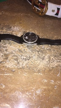round black analog watch with black leather strap