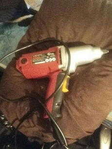 red, grey, and black corded power tool