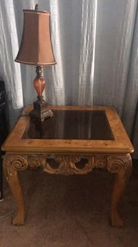Brown wooden framed glass top end table with a lamp