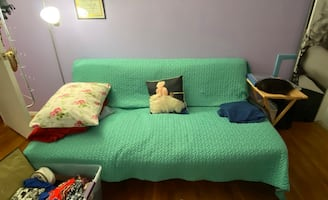 Futon w/ yellow cover and black metal frame
