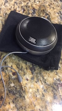 black and gray JBL bluetooth speaker on pouch