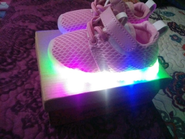 pair of pink-and-white Adidas sneakers