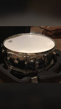 Round gray and white snare drum with case