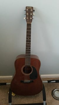 brown wooden acoustic guitar with stand