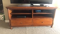 brown wooden TV stand with flat screen television Monument
