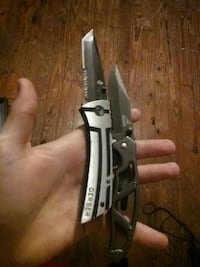 two black and silver clip-point pocket knives