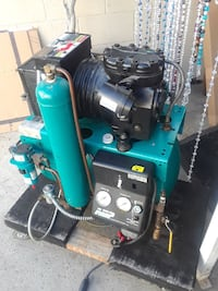 green and black industrial machine with gauge and tank