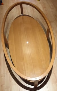 oval brown wooden framed glass-top coffee table
