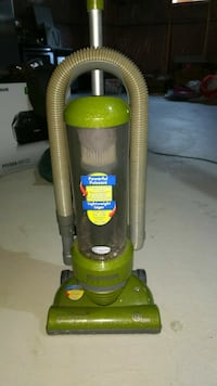 green and black Bissell upright vacuum cleaner
