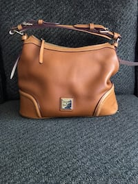 Classic Dooney and Bourke for everyday styling. You can store all your essentials. Top zip closure. Cell phone pocket!  Normal wear and tear. Minor spots on the side. Redmond, 98052