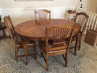 Oval brown wooden table with four chairs dining set
