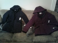 two black and maroon zip-up hooded bubble jackets